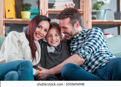 Portrait of happy loving family sitting on sofa at home