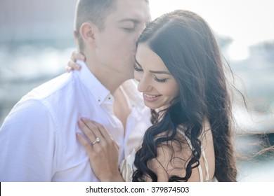 Portrait of happy loving kissing couple on sunny background. Man and woman enjoying romantic vacation on sunshine outdoors