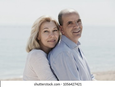 Portrait of happy loving mature couple against sea in background
