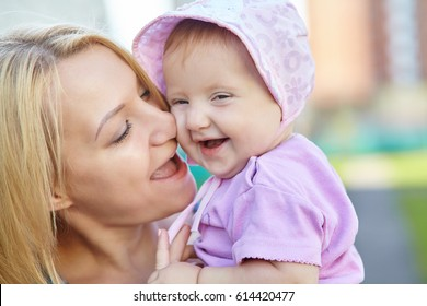 Portrait of a happy loving mother and her baby outdoors. Child and mom