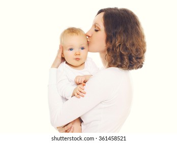 Portrait of happy loving mother kissing her baby on a white background