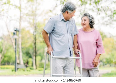 Portrait of happy loving senior Asian couple laughing while walking with walker in the park