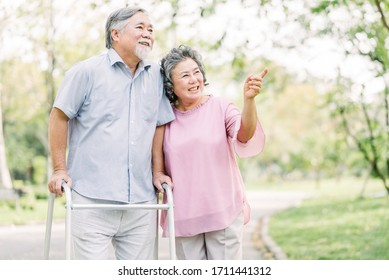 Portrait of happy loving senior Asian couple walking with walker in the park