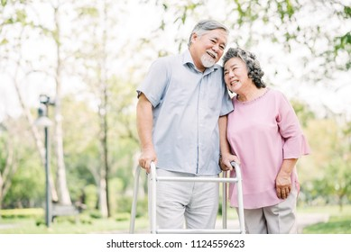 Portrait of happy loving senior couple talking a walk with walker in the park