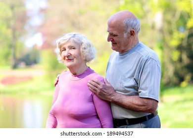 Portrait of happy loving senior couple outdoors in natural environment - active retirement concept