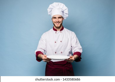 Portrait of a happy male chef cook standing with plate isolated on light blue background