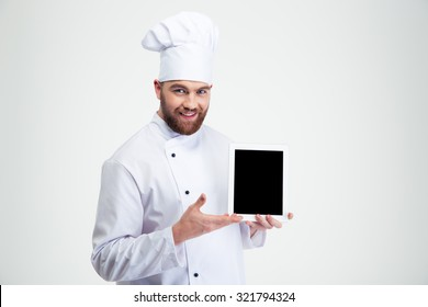 Portrait of a happy male chef cook showing blank tablet computer screen isolated on a white background