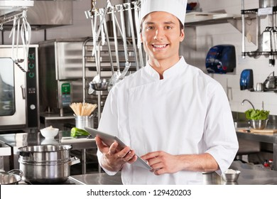 Portrait of happy male chef holding tablet computer in commercial kitchen