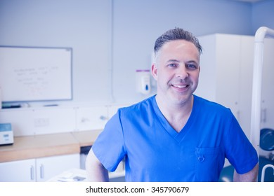 Portrait of happy male dentist posing at dental clinic