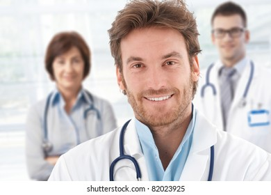 Portrait of happy male doctor with colleagues behind.?