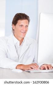 Portrait Of Happy Male Doctor Typing On Keyboard
