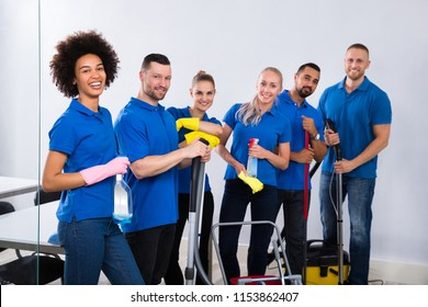 Portrait Of Happy Male And Female Janitors With Cleaning Equipment