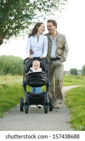 Portrait of happy male and female parents walking with their child in baby carriage