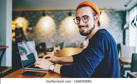 Portrait of happy male freelancer in optical eyewear smiling at camera during break from working online, positive cheerful hipster blogger sitting on publicity area with modern laptop computer