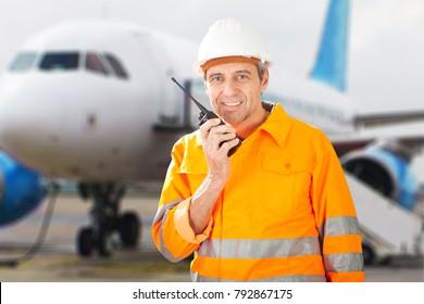 Portrait Of A Happy Male Ground Crew Talking On Walkie-talkie