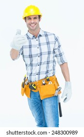 Portrait of happy male handyman gesturing thumbs up sign over white background