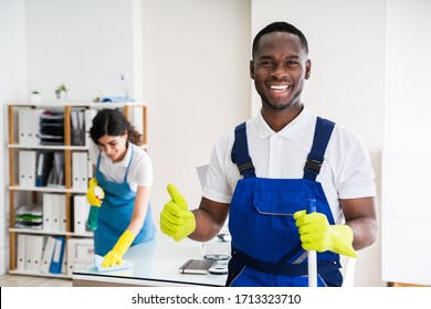 Portrait Of A Happy Male Janitor With Cleaning Equipment In Office