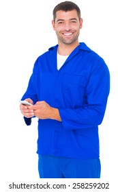 Portrait of happy male mechanic using mobile phone on white background
