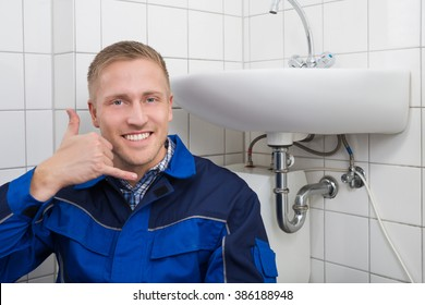 Portrait Of A Happy Male Plumber Making Call Me Gesture