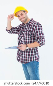 Portrait of happy male repairman wearing hard hat while holding clipboard over white background
