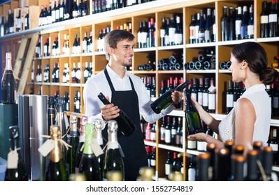 portrait of happy male seller in uniform showing bottle of wine to female customer in wine shop