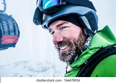 Portrait of  happy male skier with iced beard in cable car