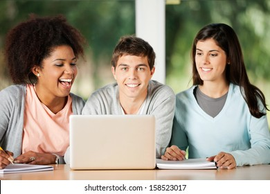 Portrait of happy male student with friends looking at laptop in classroom