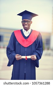 Portrait of a happy male student standing outside on his graduat