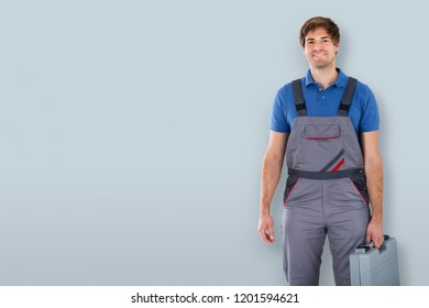 Portrait Of A Happy Male Technician Holding Toolbox On Gray Background