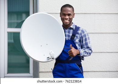 Portrait Of A Happy Male Technician With TV Satellite Dish Gesturing Thumbs Up