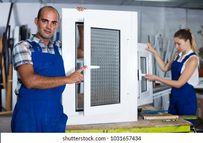 Portrait of  happy male worker with finished plastic window in assembly shop
