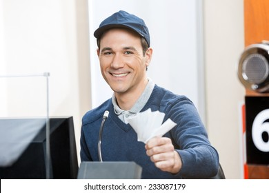 Portrait of happy male worker holding tickets at box office