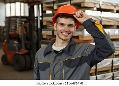 Portrait of happy male worker wearing orange helmet and protective suit touching his hardhat on metal stock. Smiling man laughing, posing and looking at camera. Pallets and forklift on background.