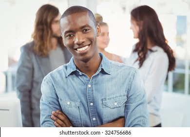 Portrait of happy man with arms crossed while coworkers discussing at office