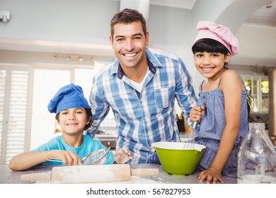 Portrait of happy man with children preparing food at home