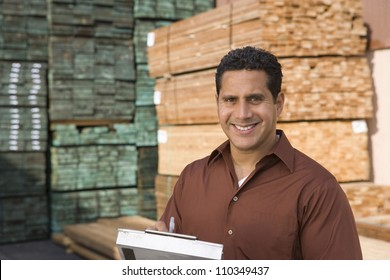 Portrait of a happy man with a clipboard in warehouse