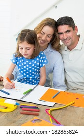 Portrait of happy man with daughter and woman coloring at home