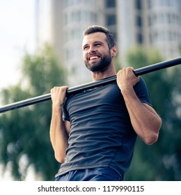 Portrait of happy man, doing pulling up exercise at horizontal bar, during workout training, outdoors. Fitness, sport, exercising and workout in city concept.