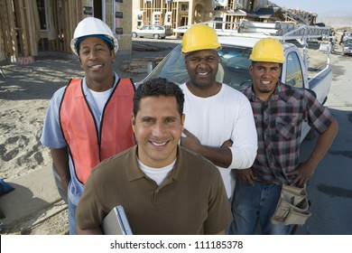 Portrait of a happy man with group of architects at construction site