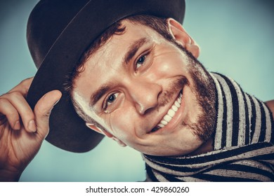 Portrait of happy man with half shaved face beard hair in hat and scarf. Smiling handsome guy on blue. Skin care hygiene and fashion. Instagram cross filter.