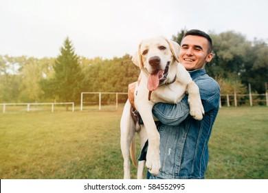 Portrait des glücklichen Mannes, der seinen Freund Hund Labrador bei Sonnenuntergang im Park hält