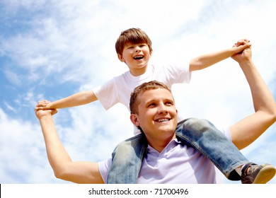 Portrait of happy man holding his son on neck on the background of sky