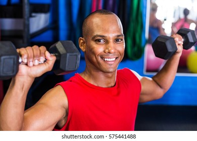 Portrait of happy man lifting dumbbell while exercising in gym