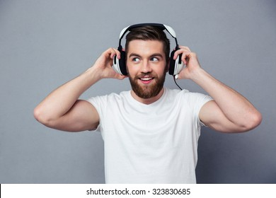 Portrait of a happy man listening the music in headphones over gray background