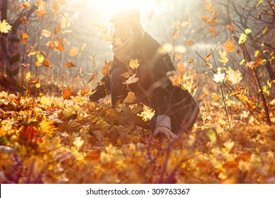 Portrait of a happy man playing with autumn leaves in forest. Retro style lens filter shot. Autumn background with sun flare light leak effect. Golden autumn