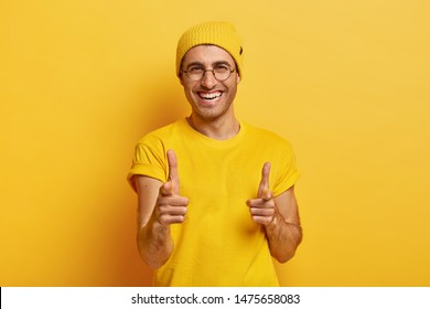 Portrait of happy man points fore fingers at camera, chooses you, looks gladfully at camera, smiles broadly, has white perfect teeth, friendly look, wears yellow clothes, poses indoor. Monochrome