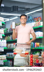 Portrait of happy man showing mobile phone screen at supermarket