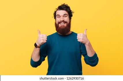 Portrait of happy man showing thumbs up over yellow background