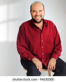 Portrait of a happy man sitting in chair against neutral background with window light