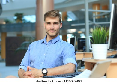 Portrait of happy man sitting at office desk, looking at camera, smiling